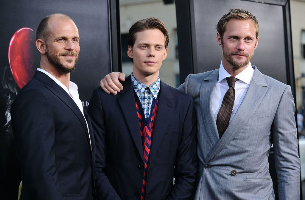 (L-R) Gustaf, Bill, and Alexander Skarsgard smiling in front of a black background