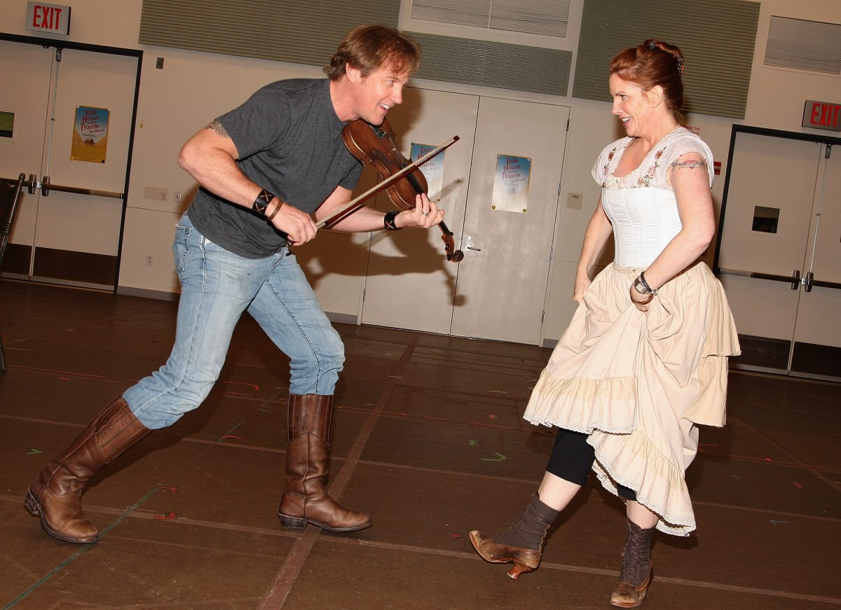 Steve Blanchard and Melissa Gilbert in rehearsal for 'Little House on the Prairie: The Musical.' Blanchard is playing the fiddle and Gilbert is dancing.