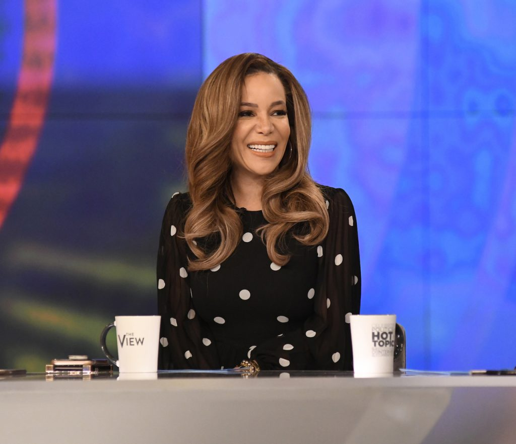 Sunny Hostin smiling in a black and white top at 'The View' table