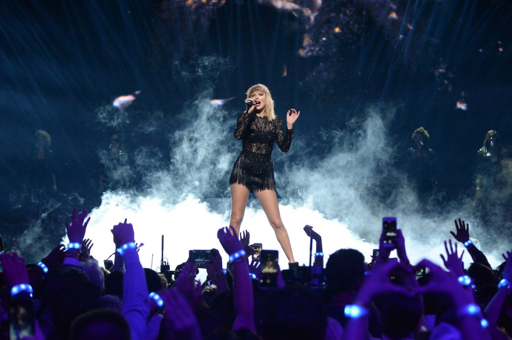 Taylor Swift performing on stage in a black outfit in 2017