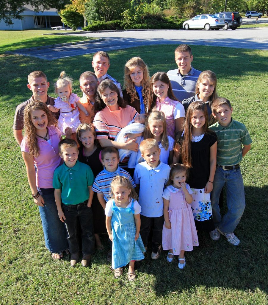 The Bates family smiles at the camera in front of their Tennessee home