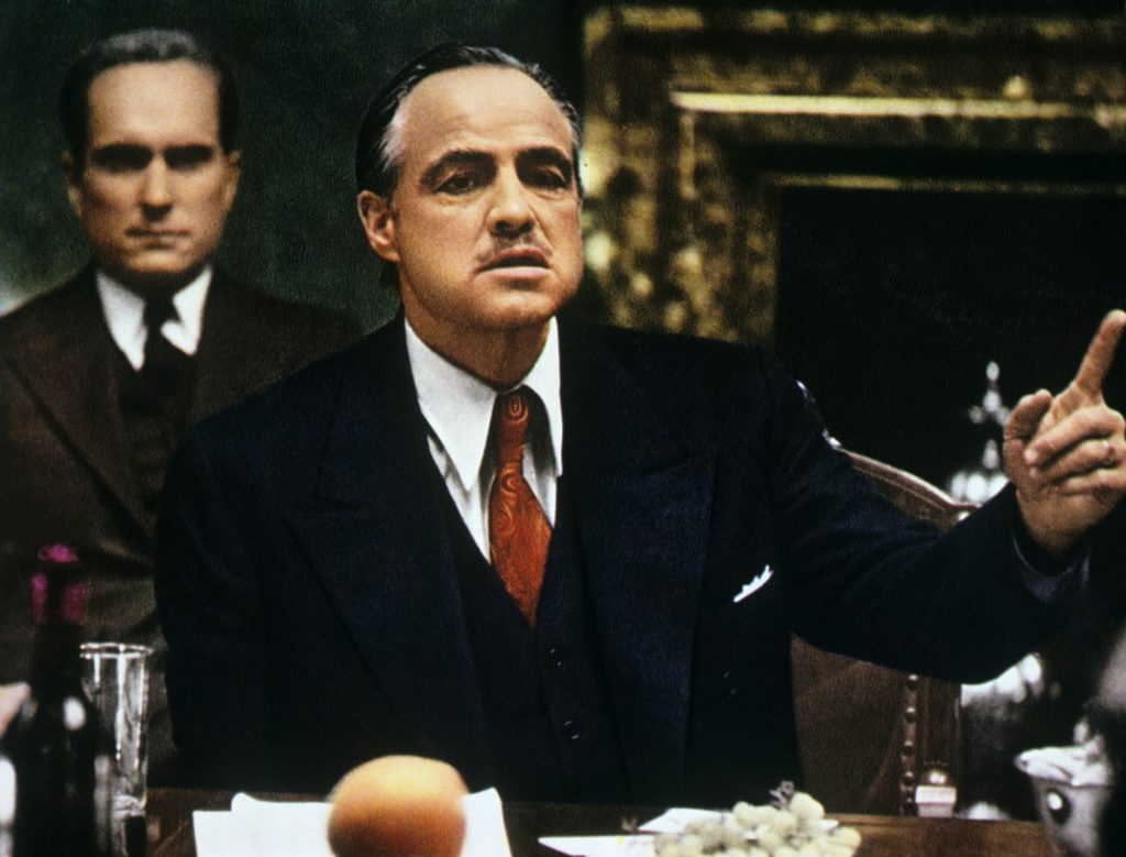 Marlon Brando in The Godfather sitting at a table