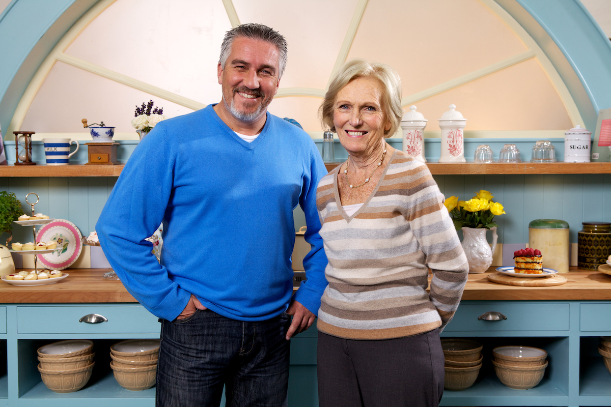 Paul Hollywood and Mary Berry smile as they stand next to each other in the tent for 'The Great British Baking Show