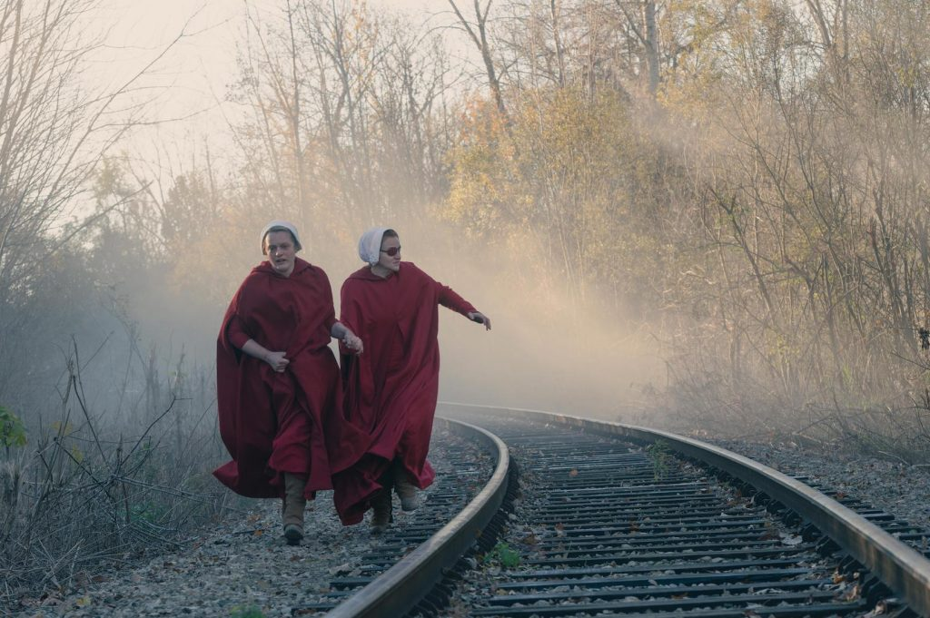 Two of the handmaids running along train tracks in 'The Handmaid's Tale' Season 4