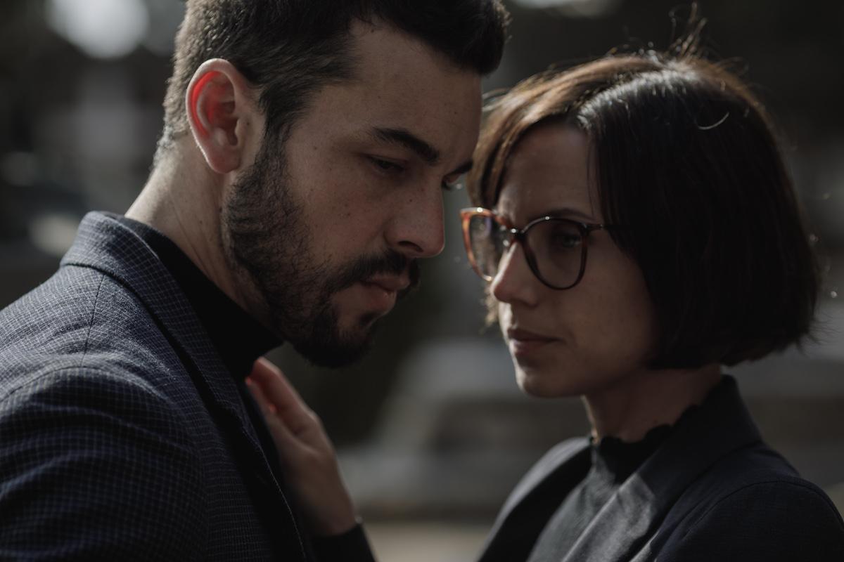 Une femme aux cheveux courts et aux lunettes touche la poitrine d'un homme