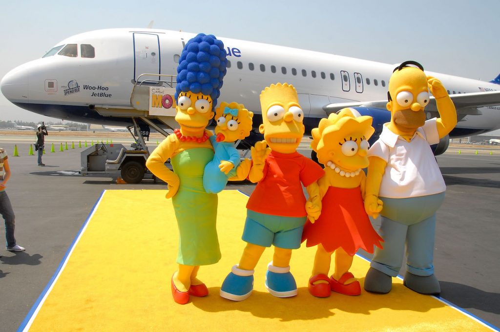 The Simpsons characters standing in front of airplane