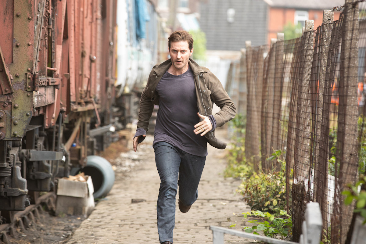 Richard Armitage running down an alley in The Stranger