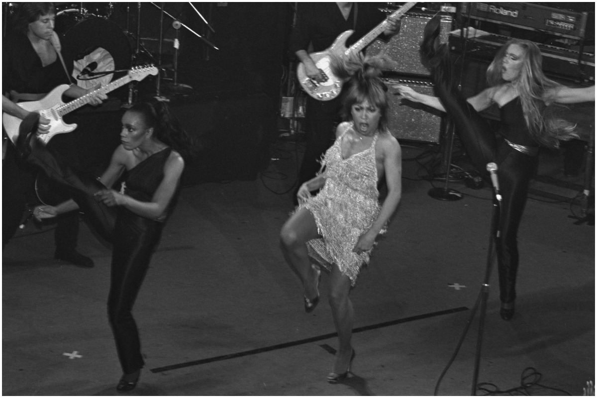 A black and white photo of Tina Turner dancing on tour.
