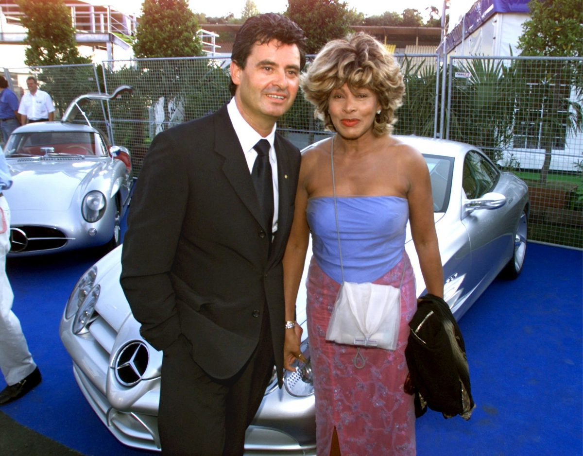 Tina Turner and Erwin Bach stand in a parking lot of fancy cars