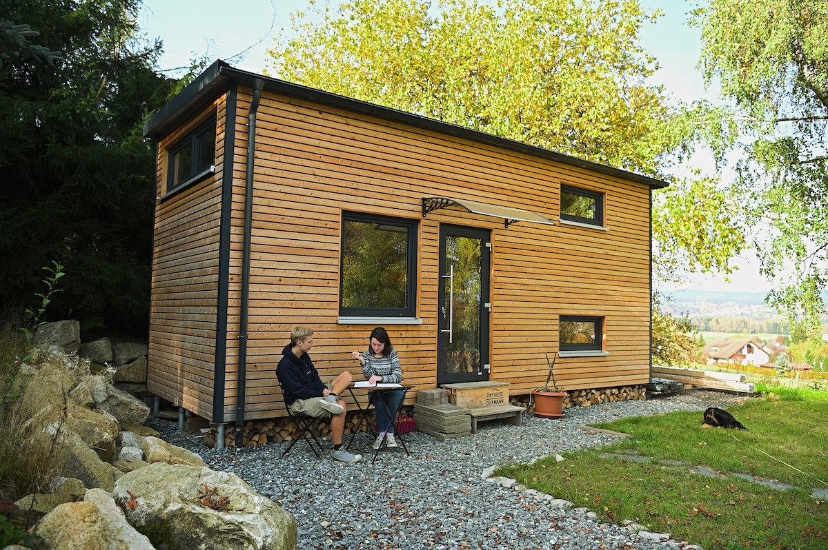 A couple sits outside a tiny house village in Germany