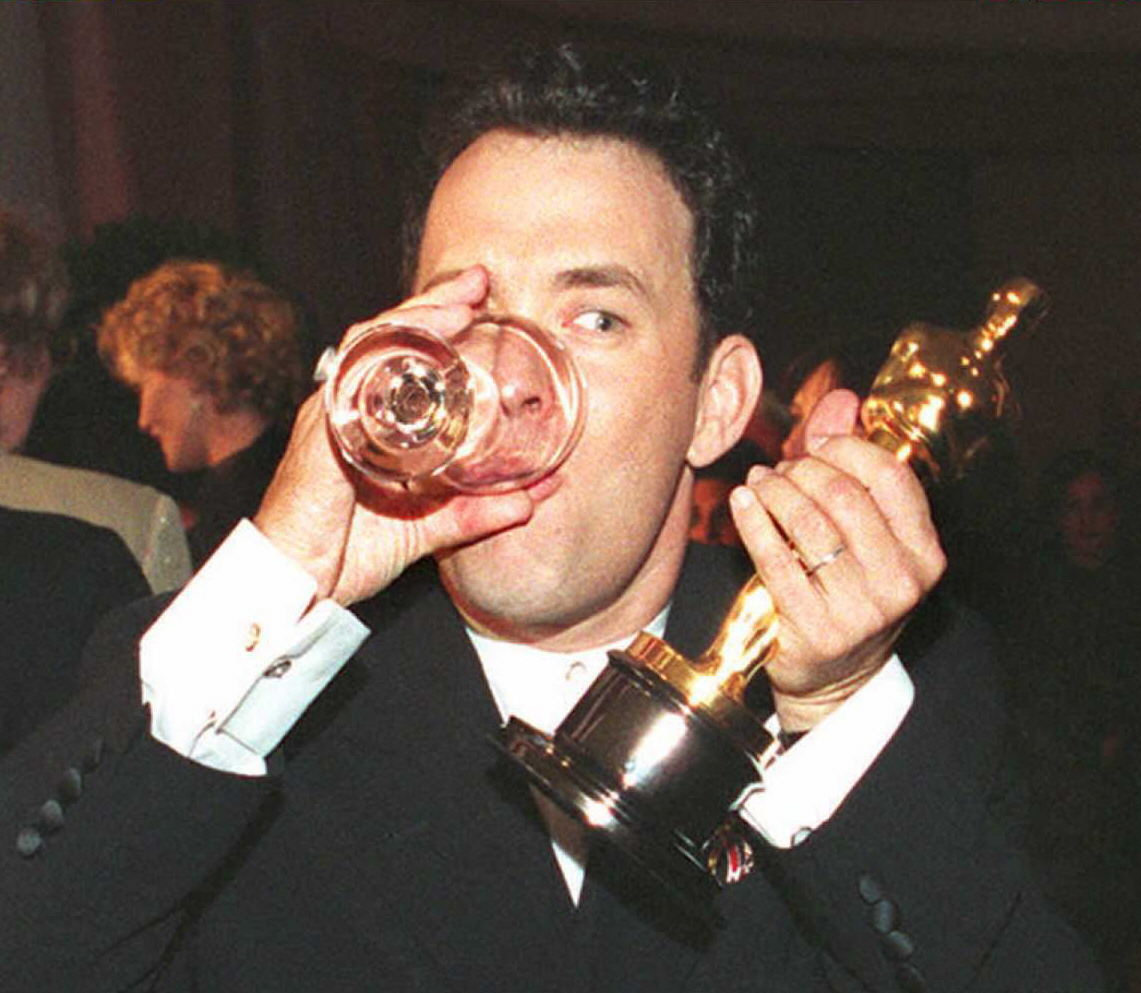 Tom hanks drinking a dink while holding his Oscar