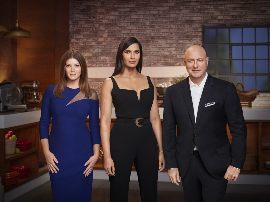 Gail Simmons, Padma Lakshmi, and Tom Colicchio, judges of 'Top Chef' Season 18, standing together in the kitchen