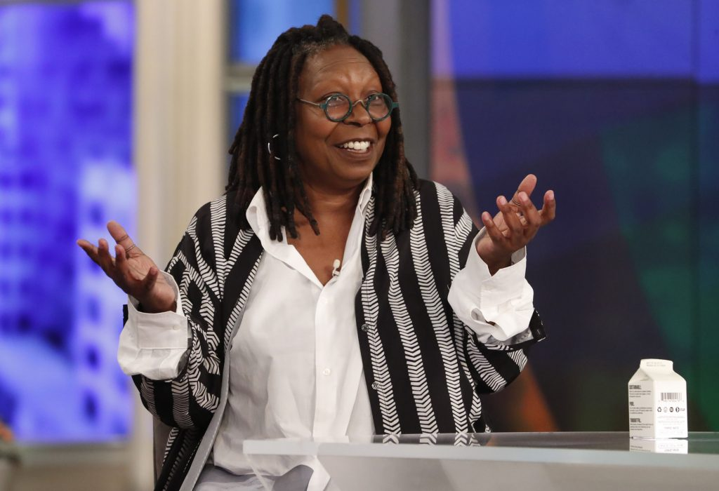 Whoopi Goldberg smiling in a white top and black-and-gray striped vest at the table of 'The View'