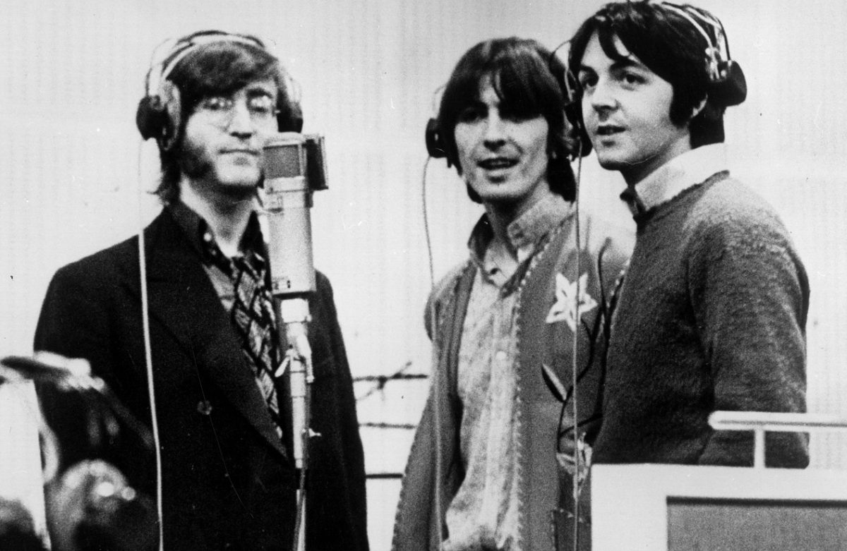 Beatles Lennon, Harrison, and McCartney stand together at a microphone in 1968