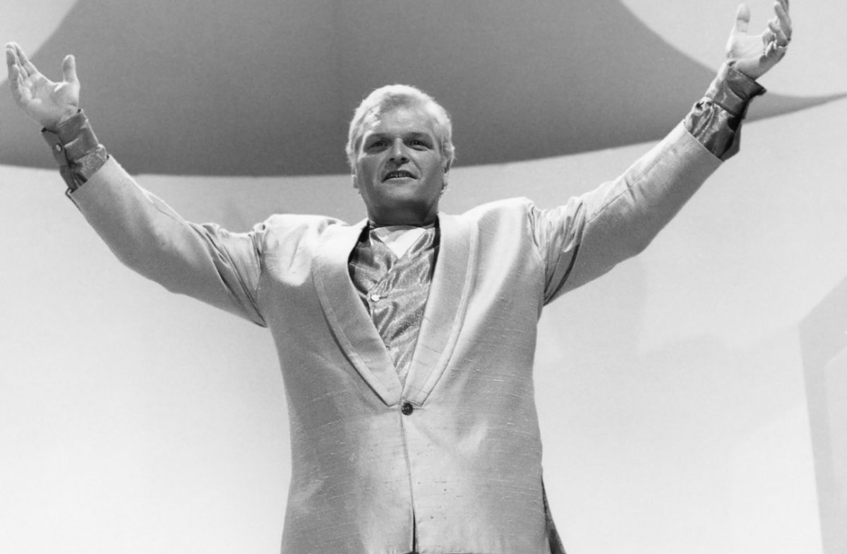 Brian Dennehy holds his hands to the sky in character as a preacher on 'Miami Vice'