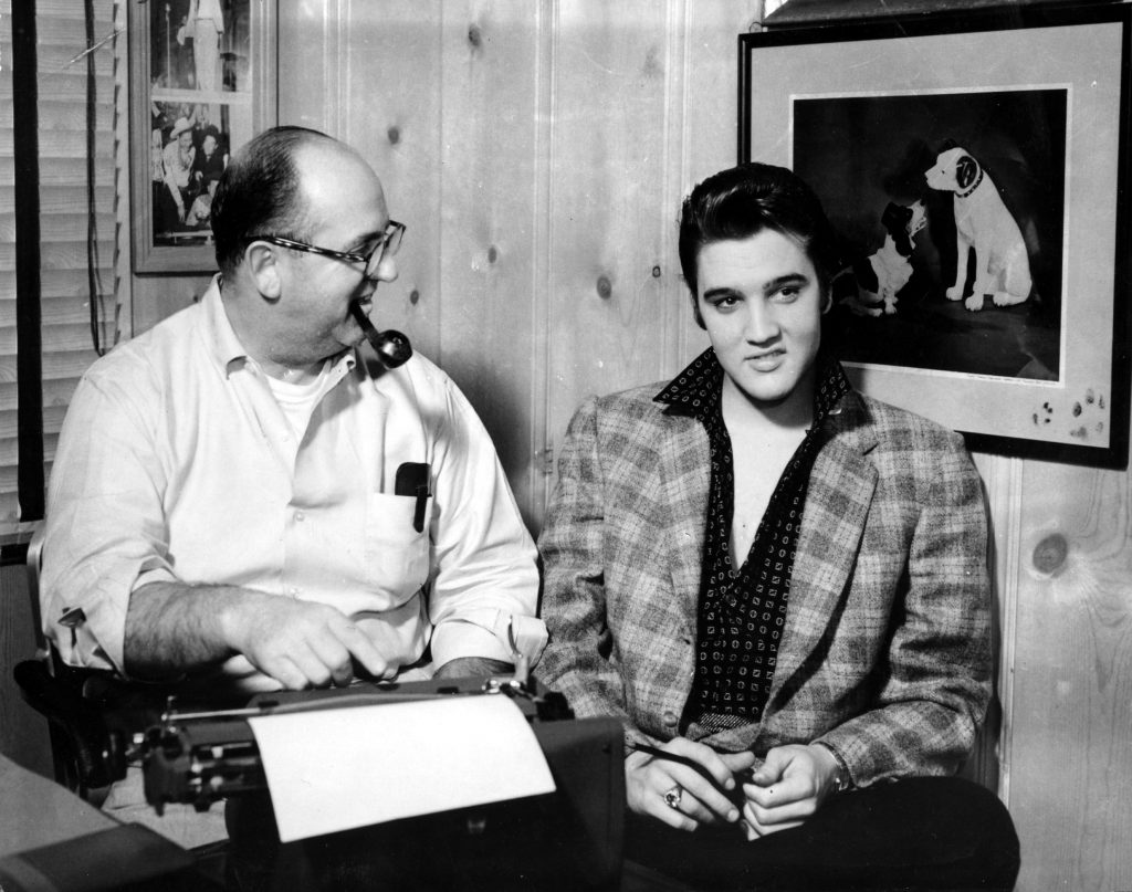 Colonel Tom Parker and Elvis Presley near an image of a dog
