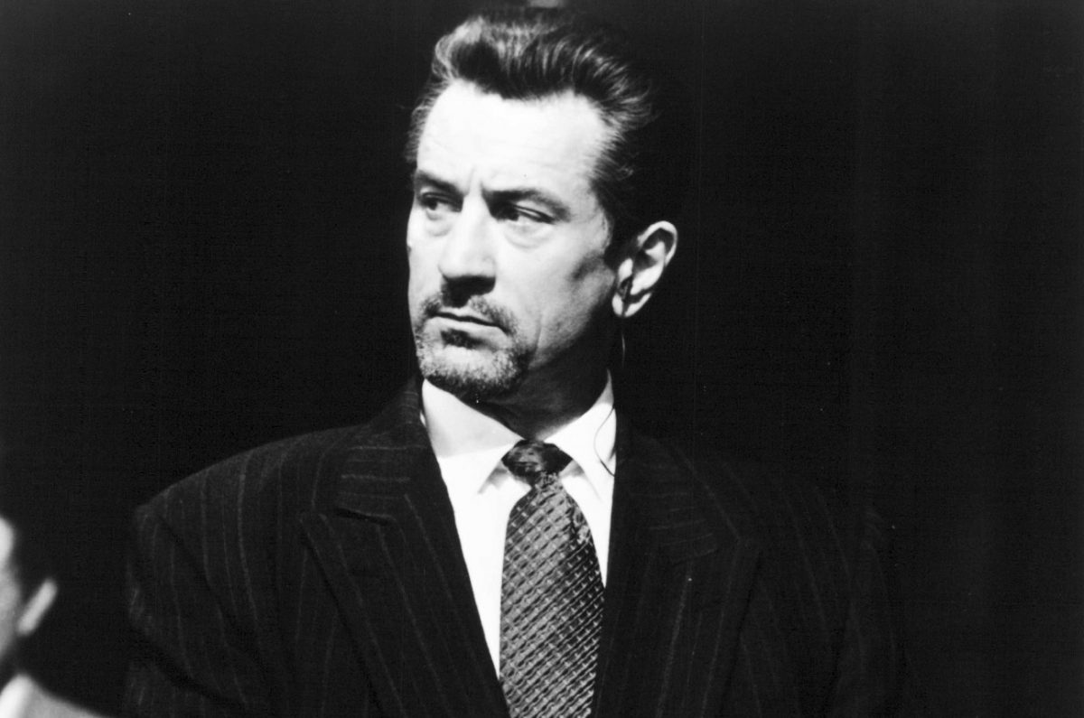 Robert De Niro wears a suit and looks off camera in a still from 'Heat'
