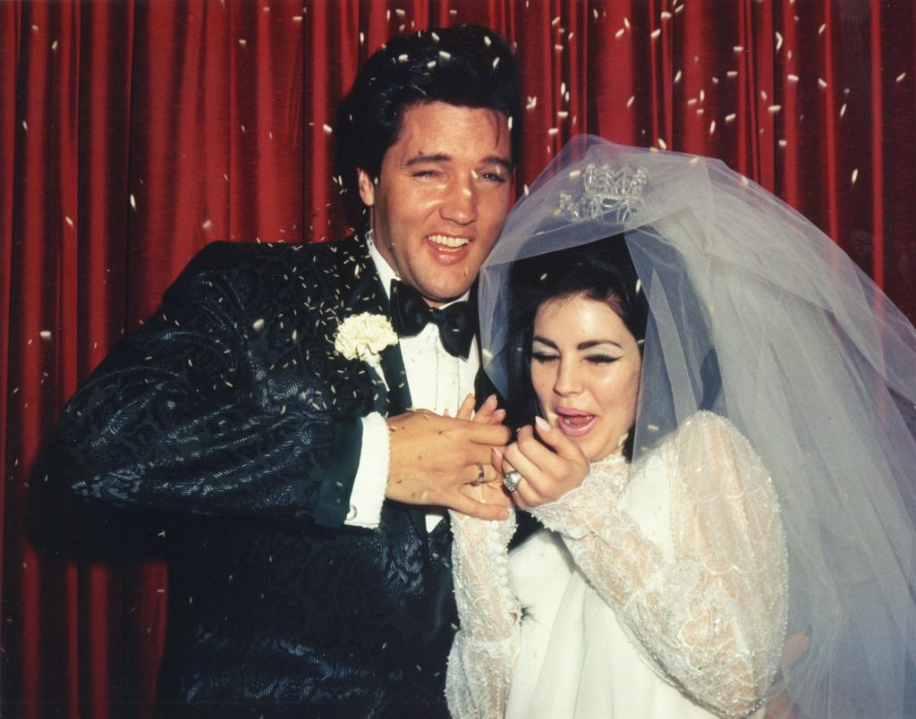 Elvis and Priscilla Presley in front of curtains