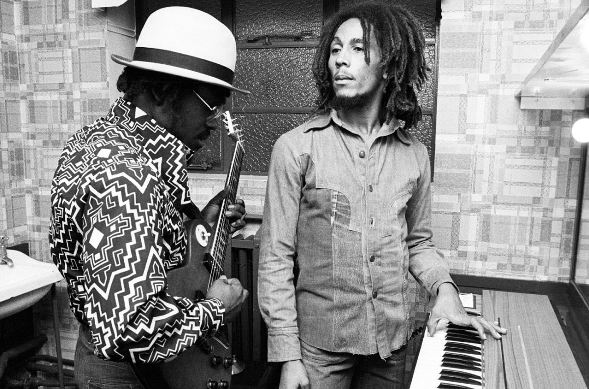 Family Man Barrett plays guitar as Bob Marley stands with his hand on a keyboard