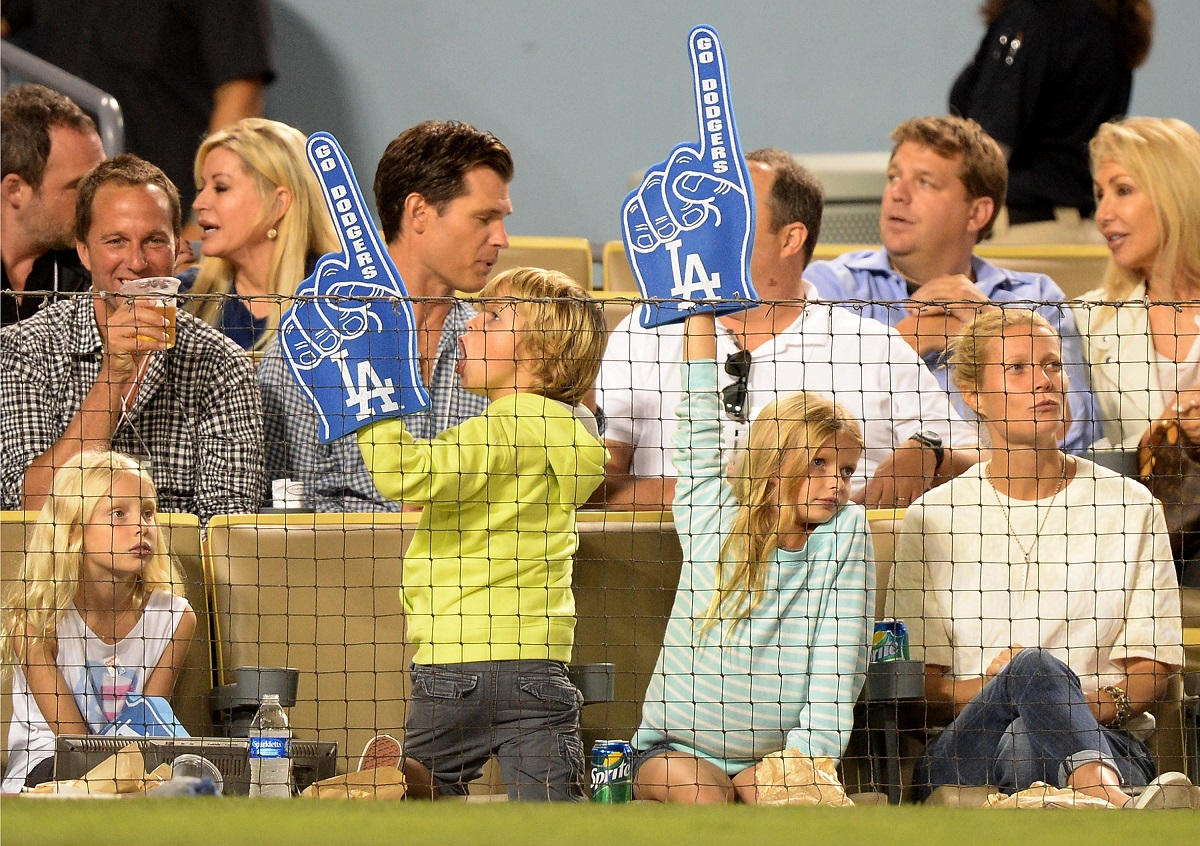 Gwyneth Paltrow (far R) with Moses and Apple Martin (L-R with foam fingers) on September 11, 2013, in Los Angeles, California.