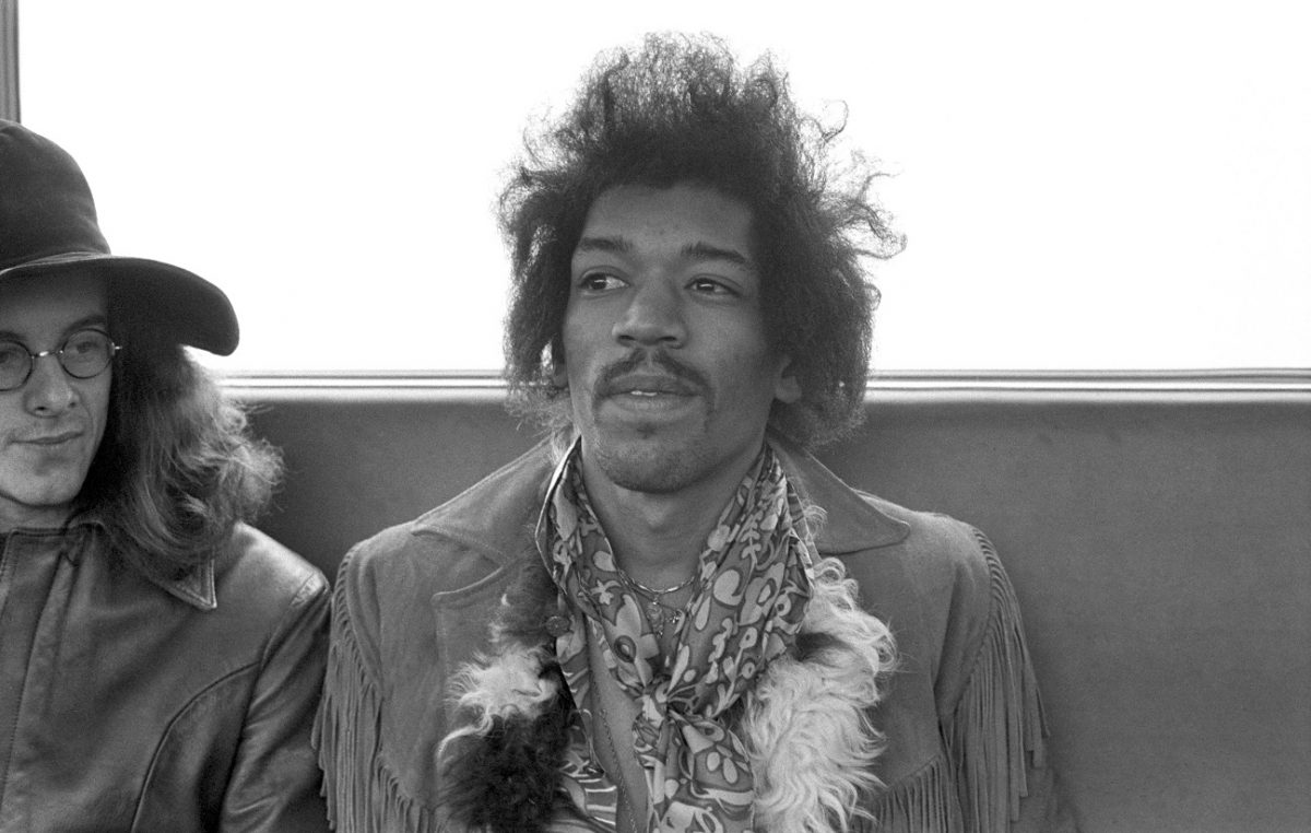 Jimi Hendrix smiles and looks off-camera with Noel Redding to his right