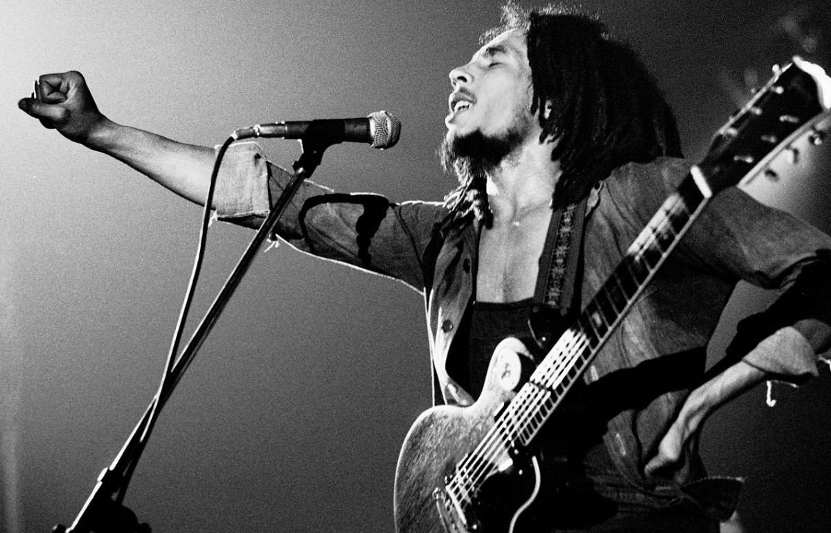 Bob Marley, eyes closed, holds his fist out to the crowd during a 1976 performance
