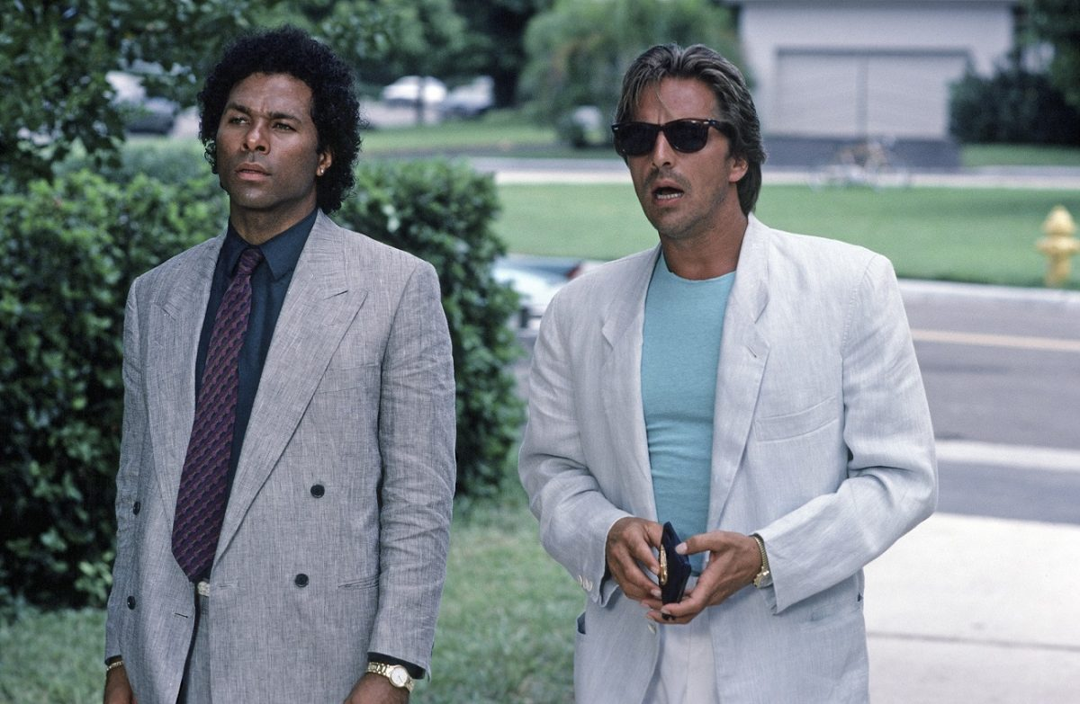 Don Johnson stands with his mouth agape in character as Sonny Crockett. Philip Michael Thomas stands to his right.