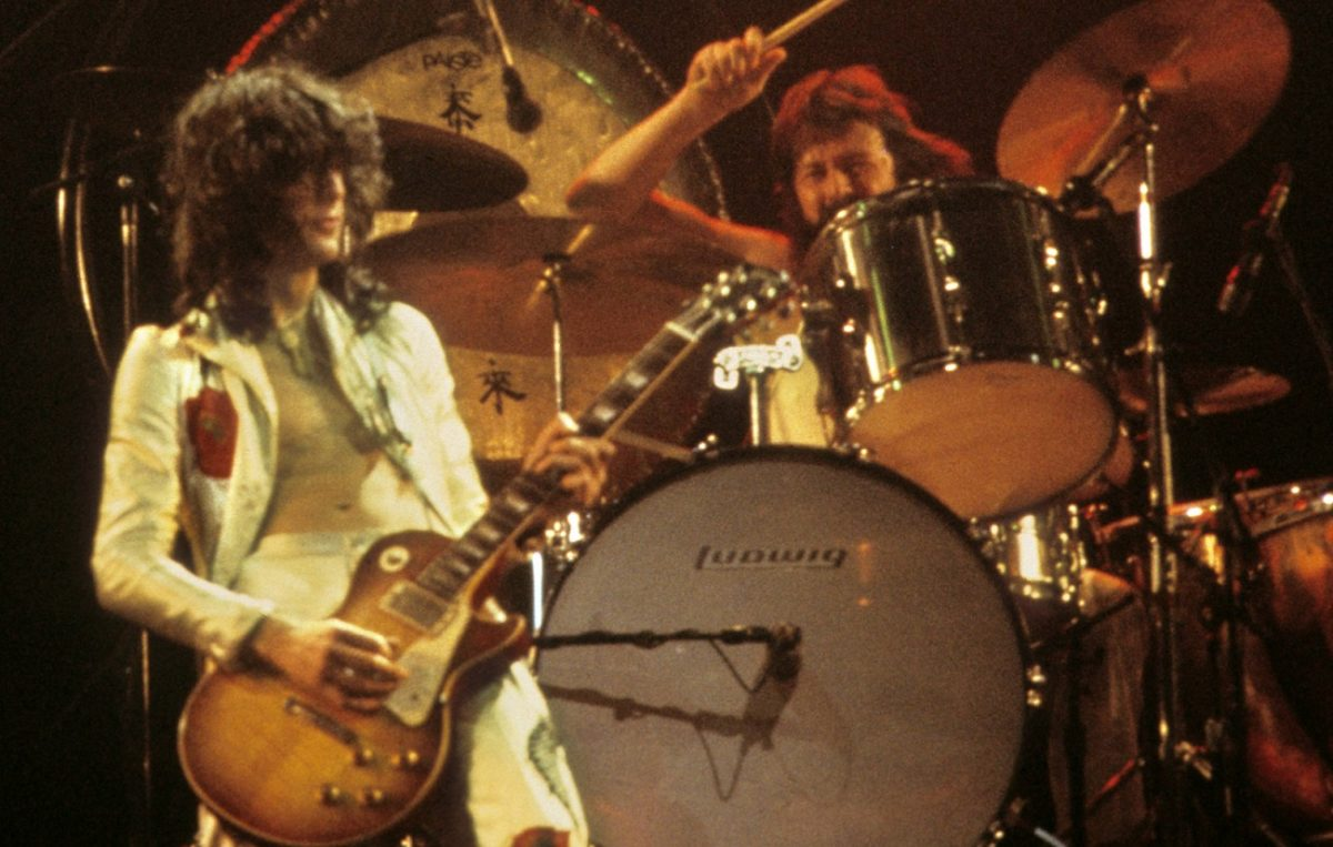 Jimmy Page plays guitar while John Bonham swings his drum stick at his drum kit during a 1977 Led Zeppelin performance
