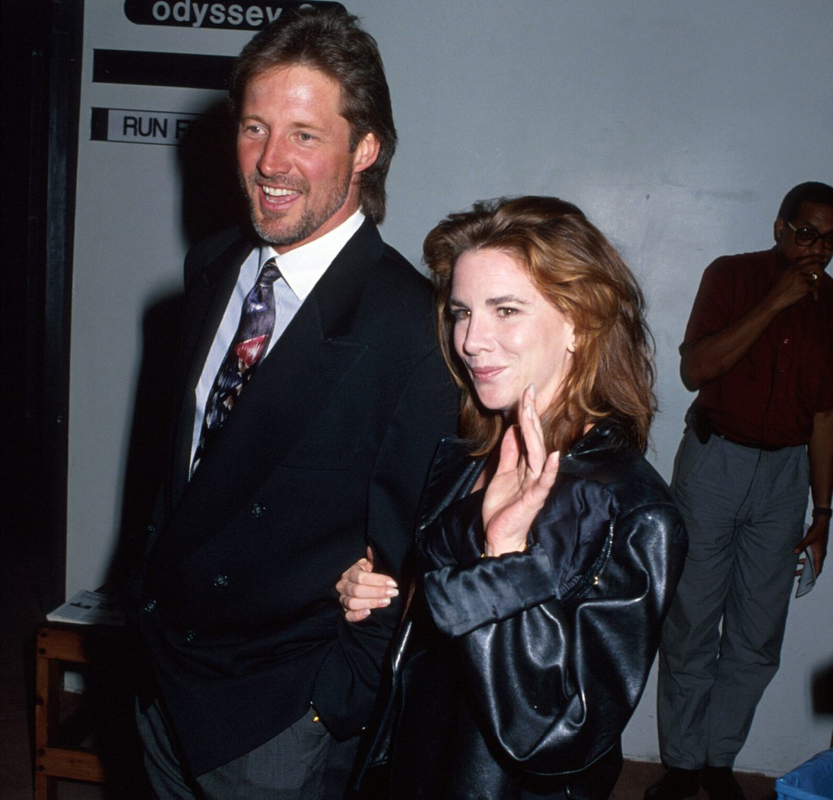 Bruce Boxleitner and Melissa Gilbert holding hands out in public. Gilbert is waving to someone to the left of the camera.