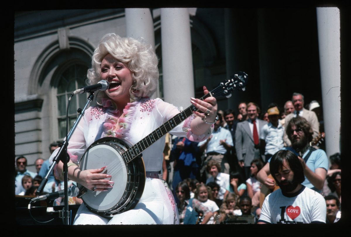 Dolly Parton playing banjo and singing for a live audience.