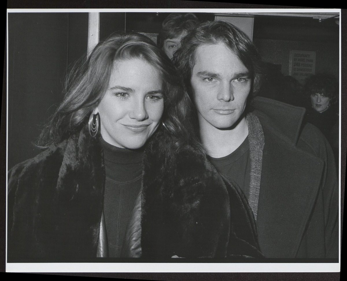 Melissa Gilbert and Bo Brinkman in black and white. Brinkman is in a fur coat and Brinkman is standing closely behind her.