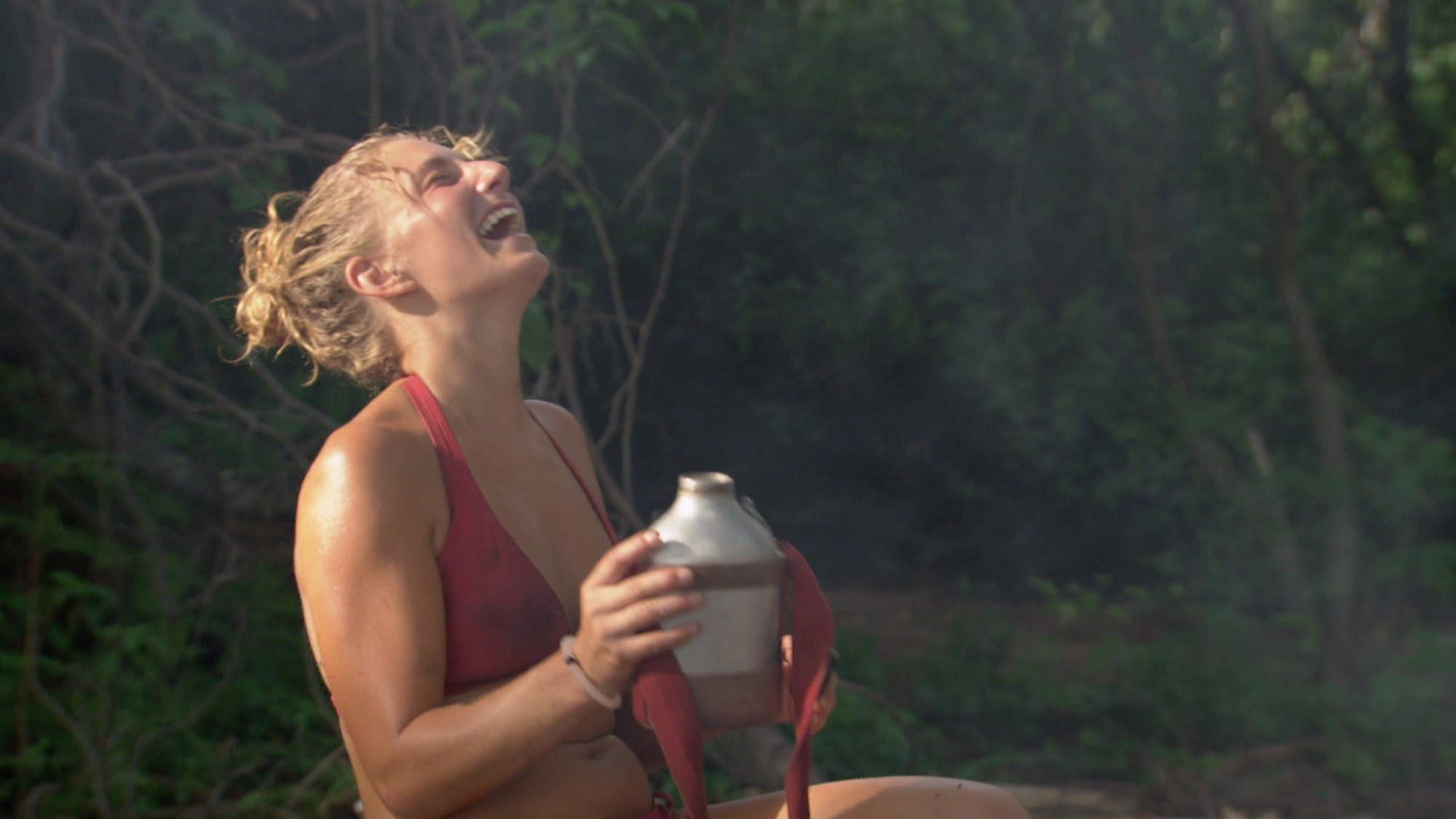 Jenn Brown during the ninth episode of  Survivor: Worlds Apart, laughing and holding a vase or urn