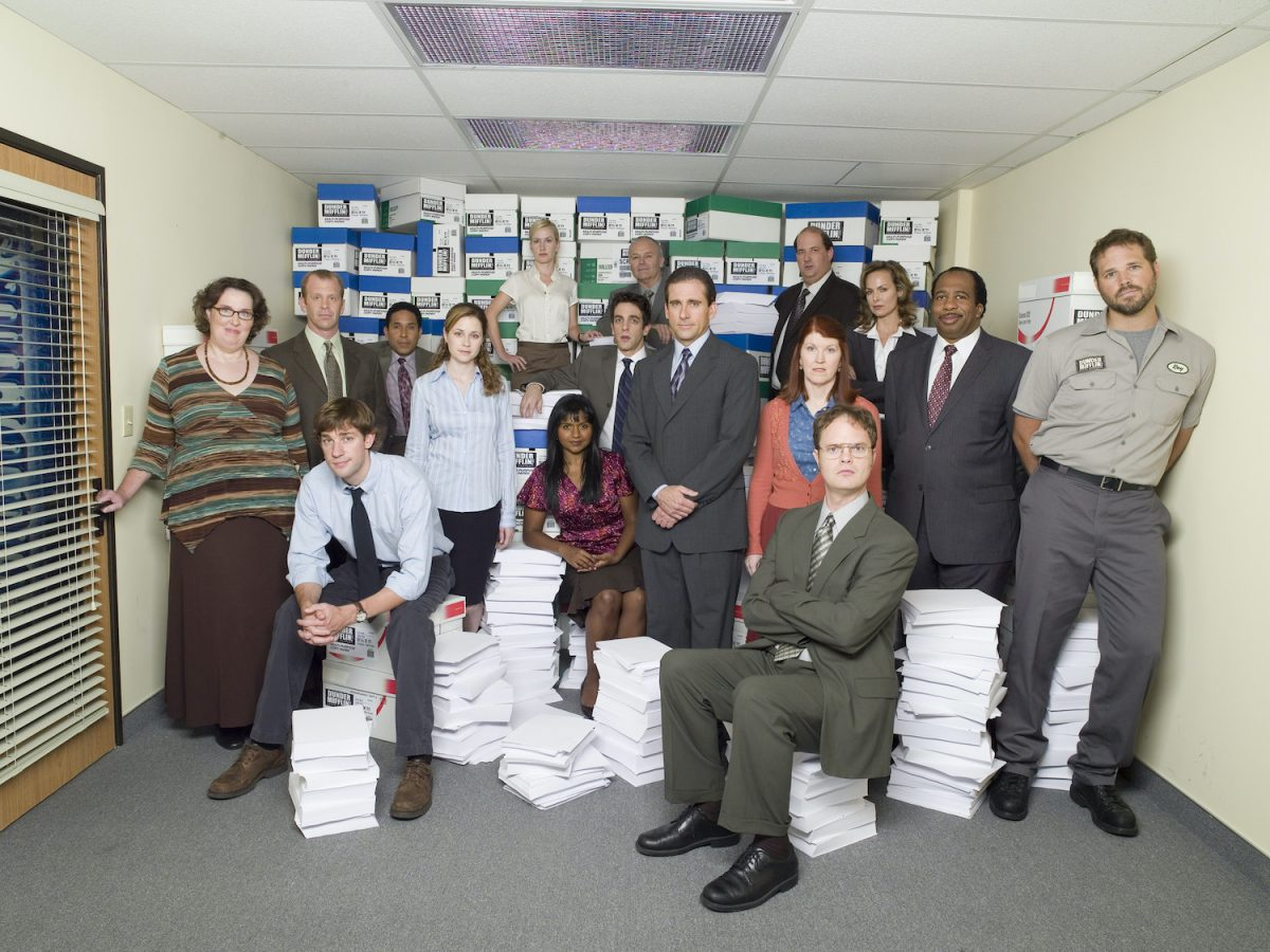 'The Office' cast poses in character amid piles of paper.