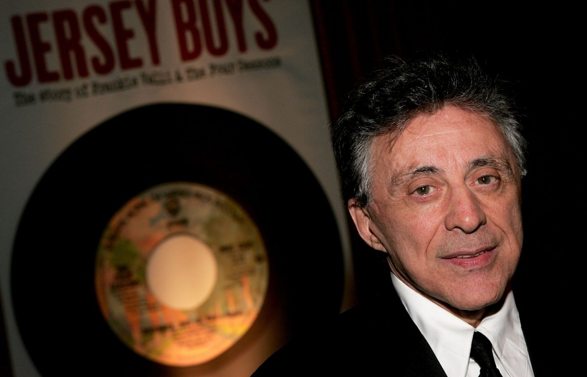 Frankie Valli looks at the camera with a 'Jersey Boys' poster behind him, 2005