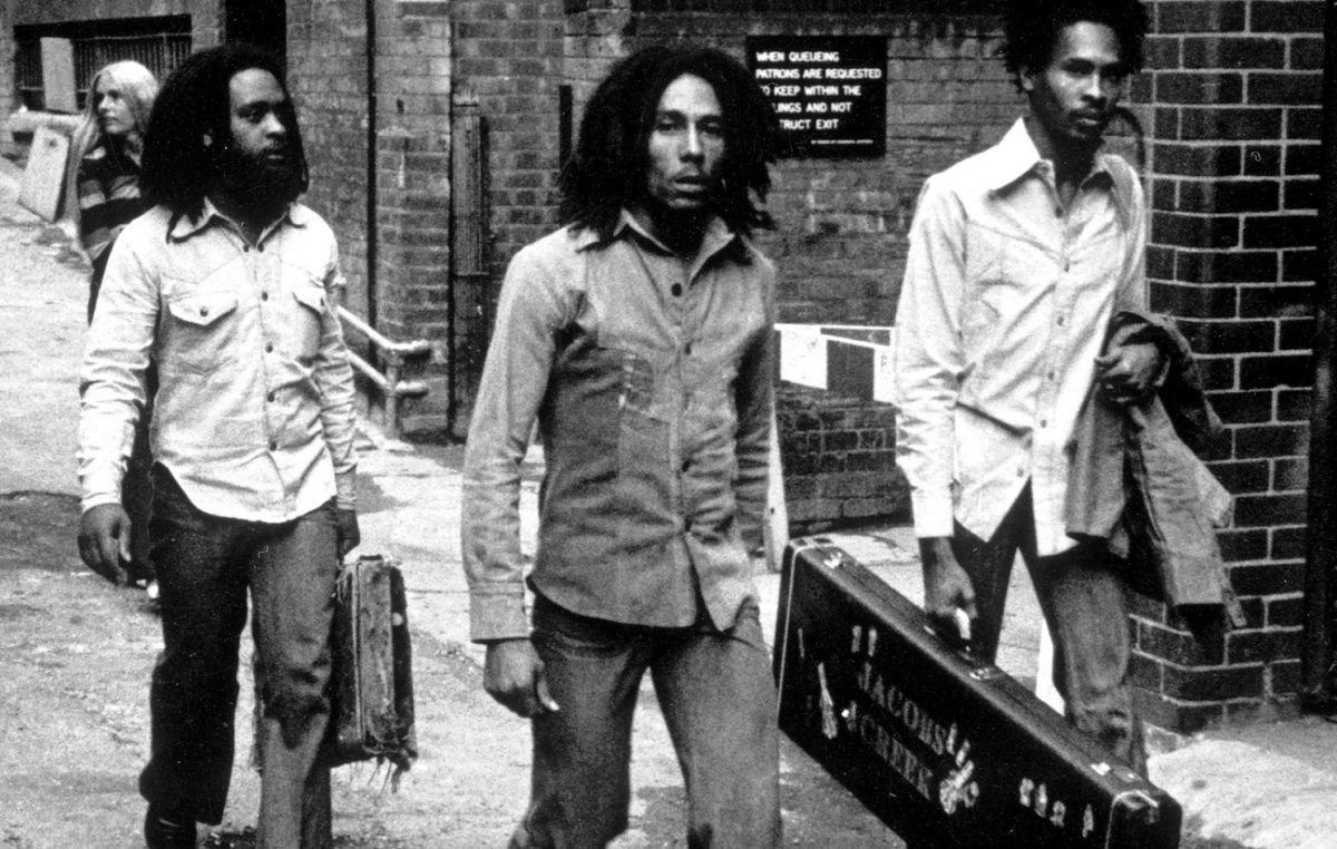 Bob Marley, with two bandmates on either side, looks into the camera en route into a British club