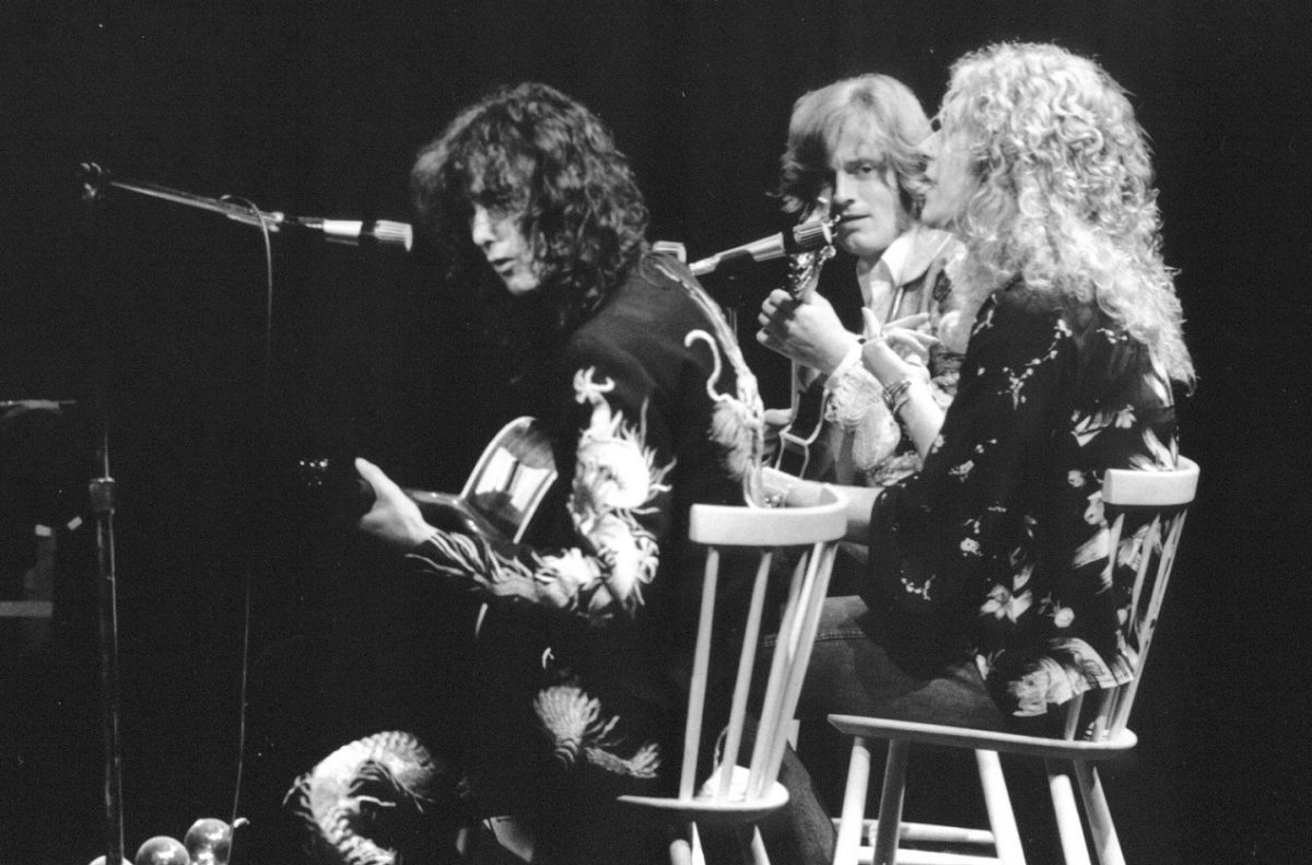 3 members of Led Zeppelin perform on stage while seated