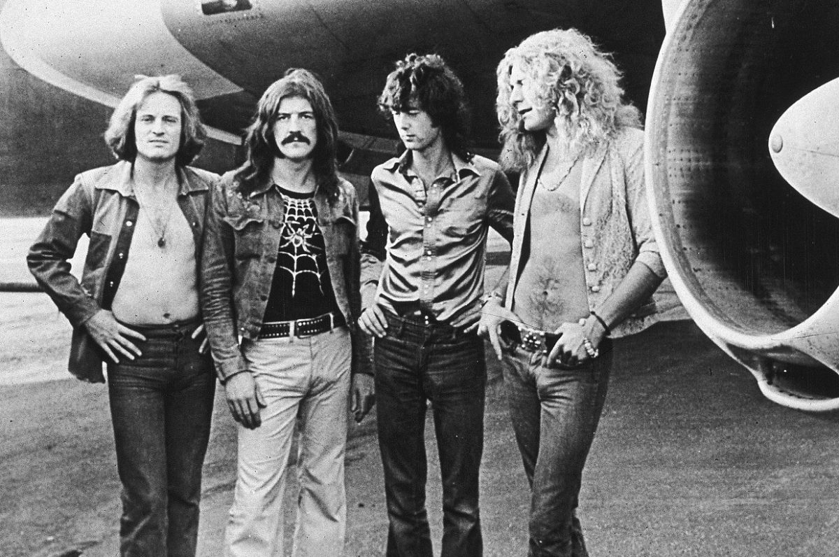 Led Zeppelin posing in front of the wing of the band's airplane in 1973
