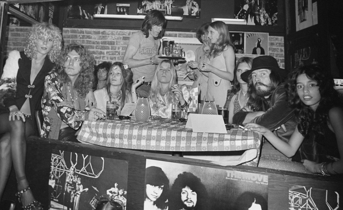 Members of Led Zeppelin surrounded by groupies in a Los Angeles club, 1972