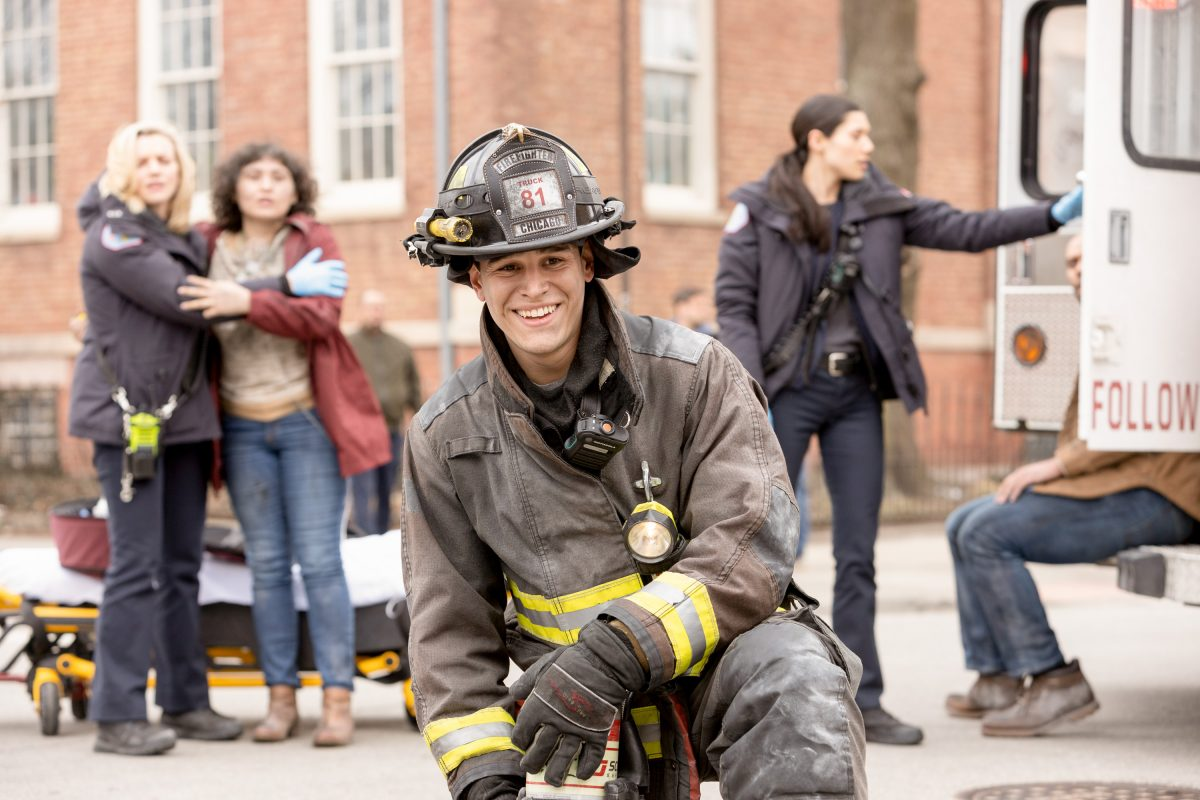 Alberto Rosende as Blake Gallo on 'Chicago Fire' kneels at the scene of an accident.