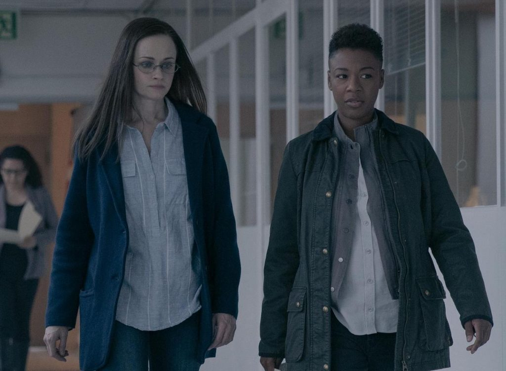 Alexis Bledel as Emily and Samira Wiley as Moira walking in a naturally lit hallway in 'The Handmaid's Tale' Season 4