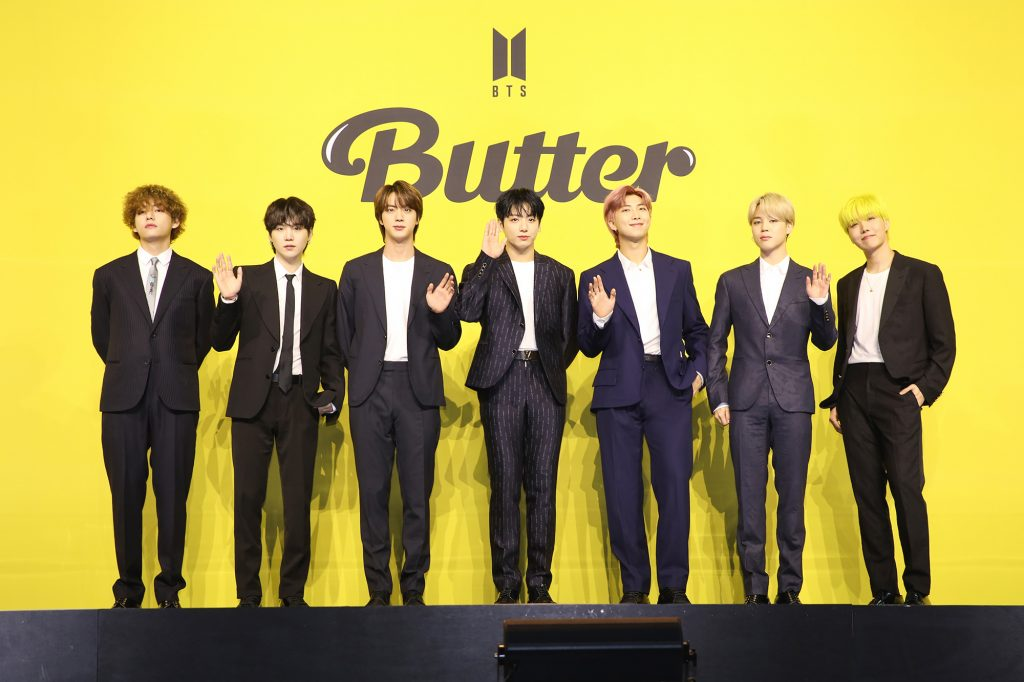 V, Suga, Jin, Jungkook, RM, Jimin, and J-Hope of BTS pose in front of a yellow backdrop at the band's press conference for their song 'Butter'
