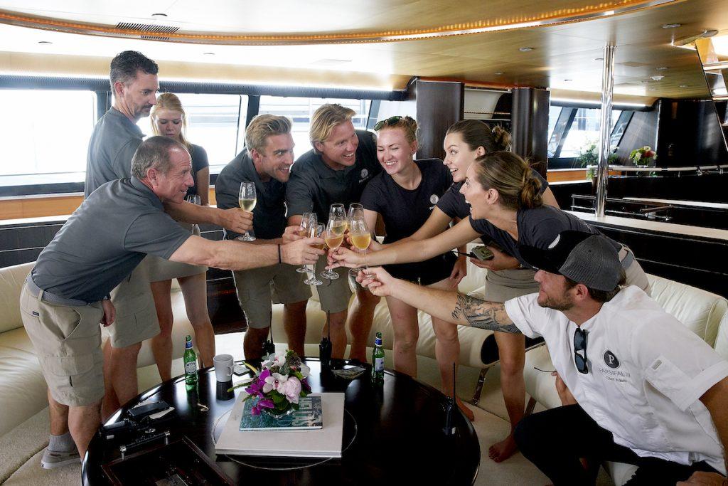 Below Deck Sailing Yacht Season 1 crew toast to a successful charter. Captain Glenn Shephard, Byron Hissey, Madison Stalker, Parker McCown, Paget Berry, Ciara Duggan, Georgia Grobler, Jenna MacGillivray, Adam Glick