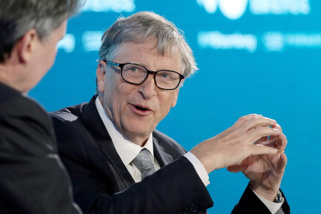 Bill Gates age 64 sitting against a blue background while speaking at a conference