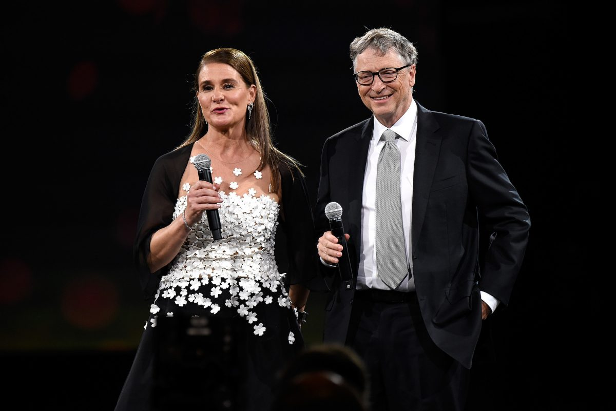 Melinda Gates and Bill Gates speaking to a crowd against a black background