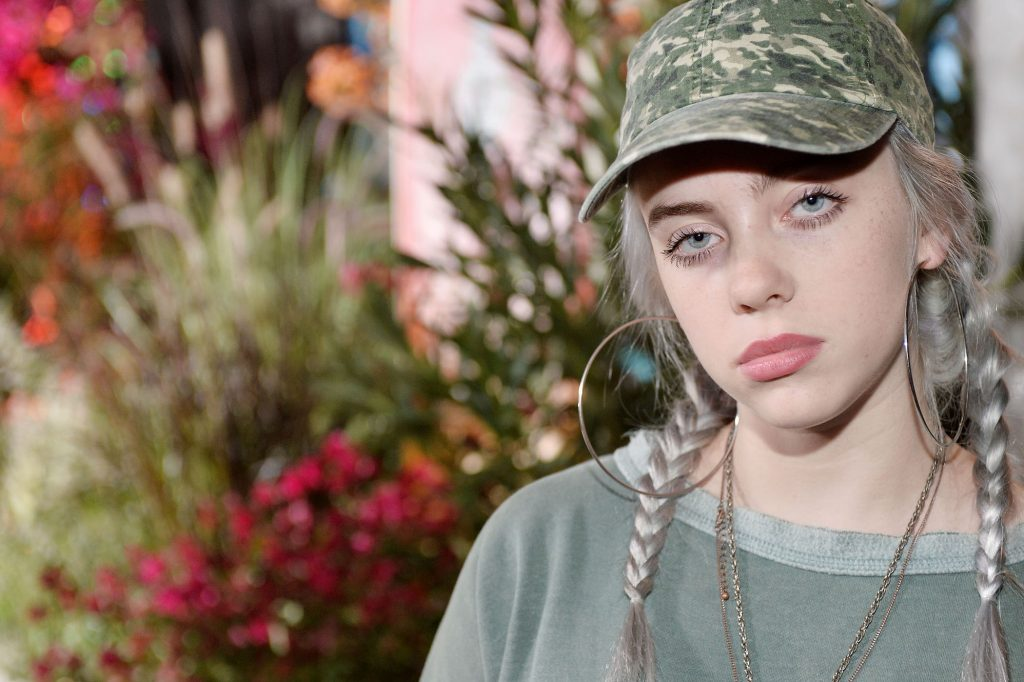 A close-up of Billie Eilish wearing a camo hat and a green shirt at a Teen Vogue event