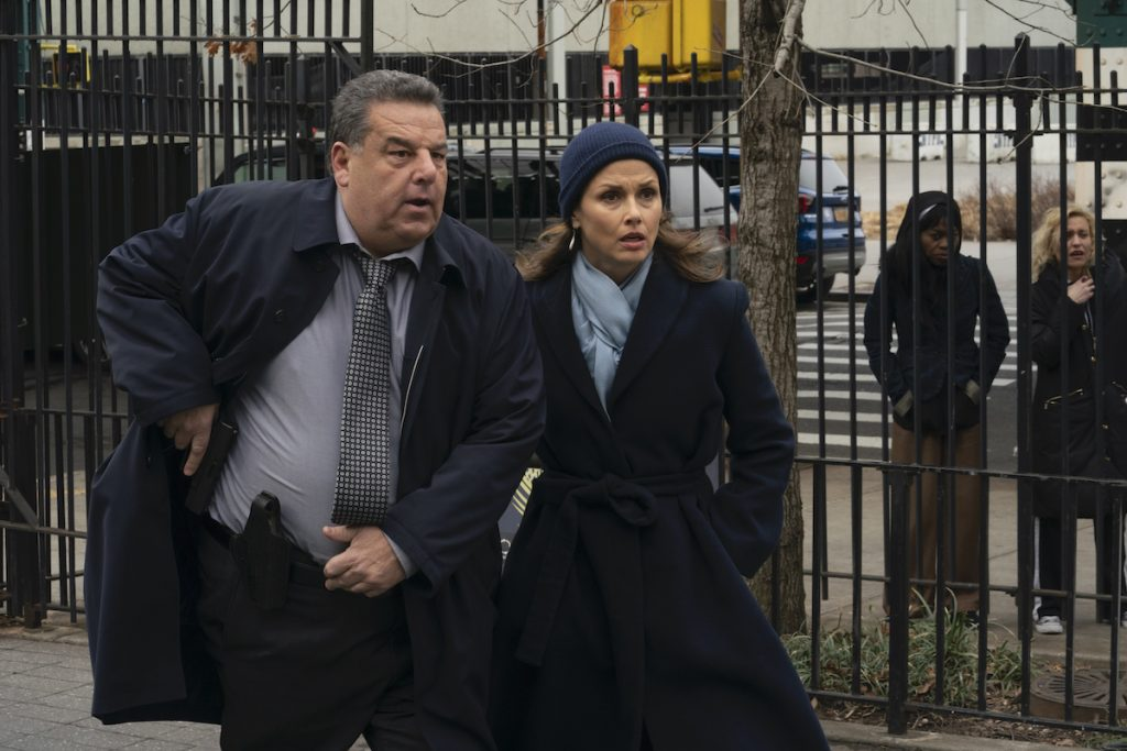 Steven Schirripa as Det. Anthony Abetemarco and Bridget Moynahan as Erin Reagan stand next to each other in a park in winter coats on 'Blue Bloods'