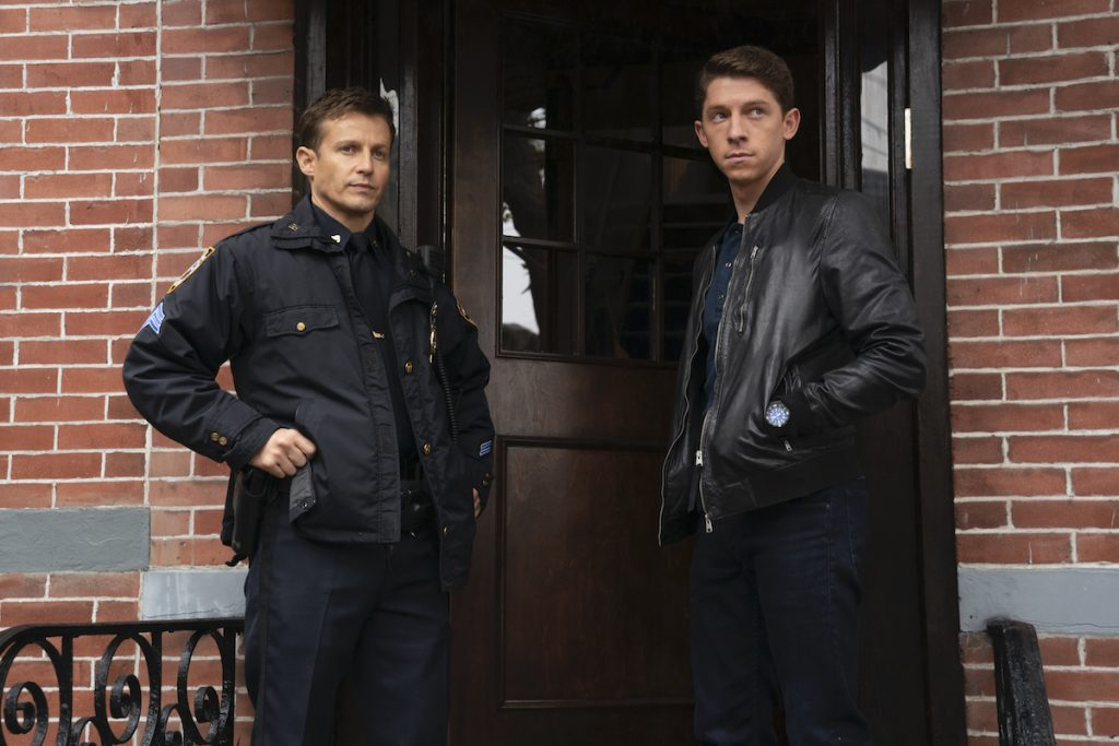 Will Estes as Jamie Reagan in a cop uniform and Will Hochman as Joe Hill in a black leather jacket stand at a door on 'Blue Bloods'