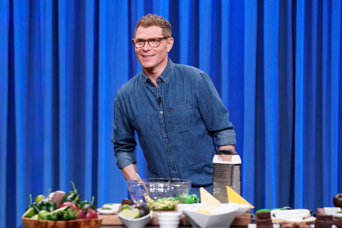 Bobby Flay smiles during a cooking segment on 'Late Night with Seth Meyers' Season 7 in 2019