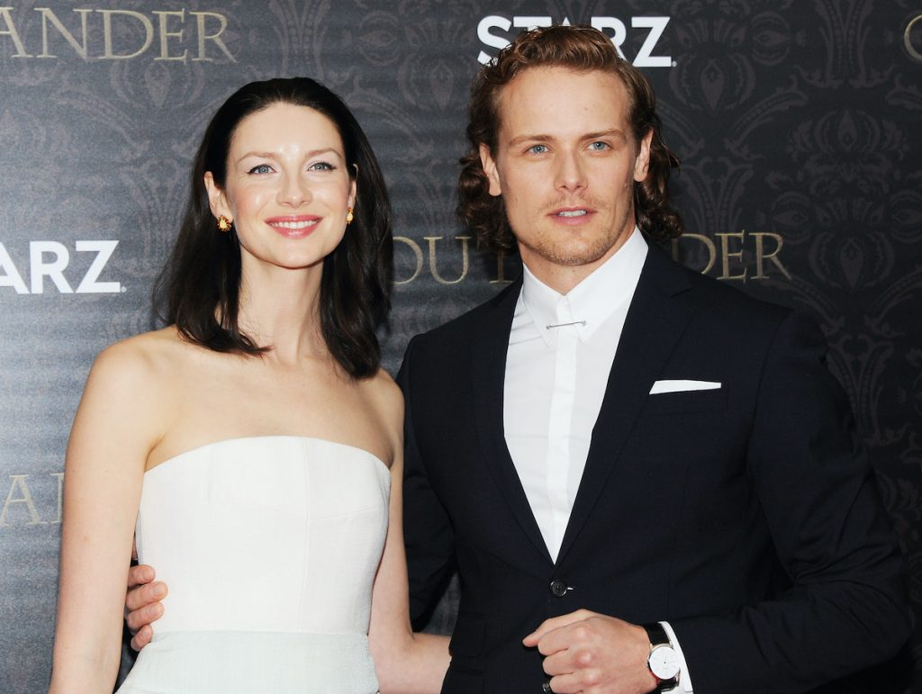 Caitriona Balfe smiles in a strapless white dress and poses next to Sam Heughan, who's wearing a blue suit. They're standing in front of a grey ornate backdrop that says 'Outlander' and 'STARZ.'