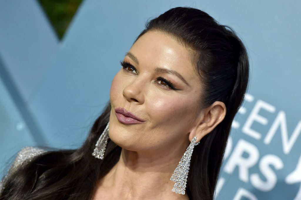 Catherine Zeta-Jones smirks with her hair half pulled back. She wears long dangling diamond earrings and stands in front of a light blue backdrop.